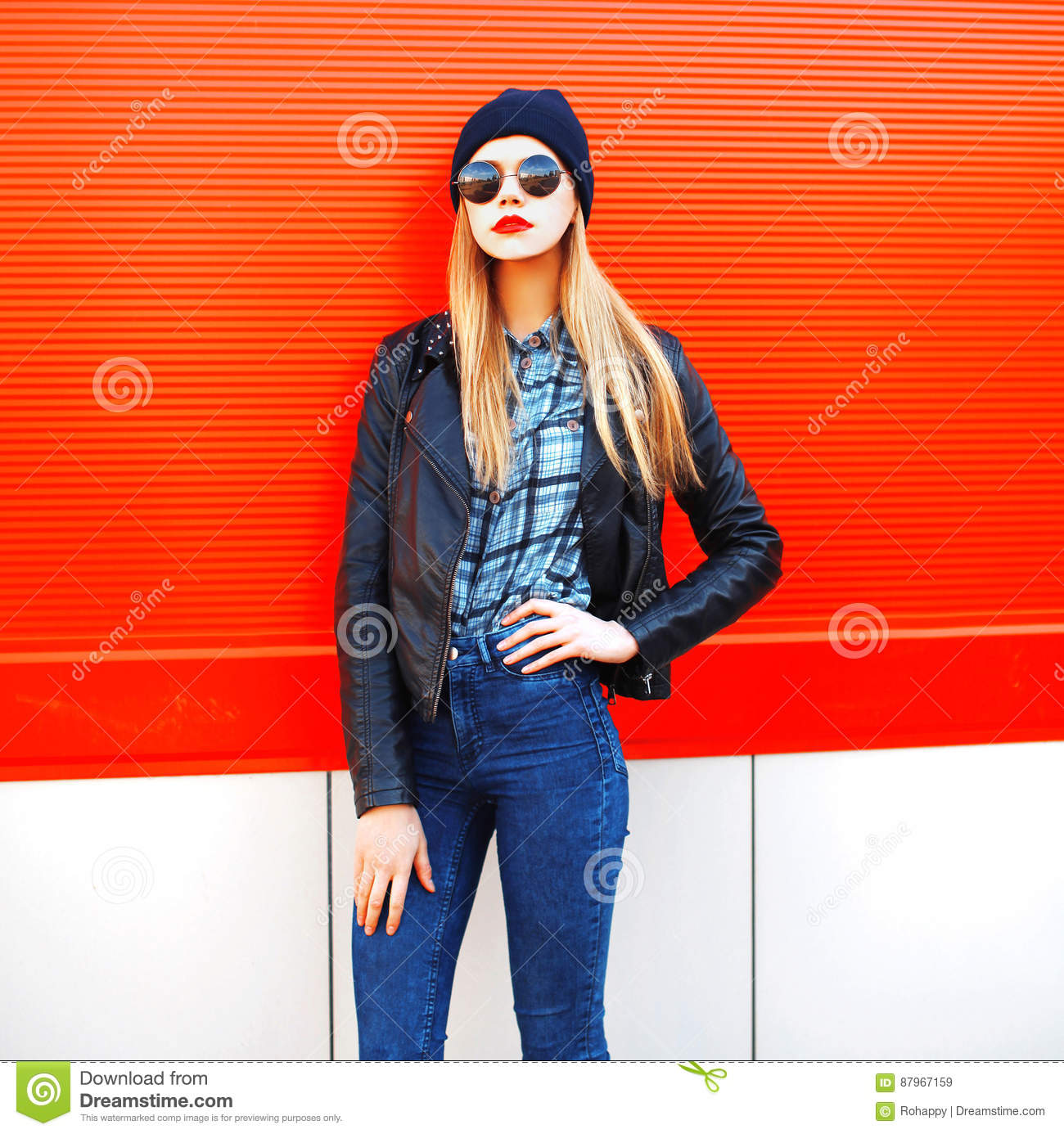 Fashion portrait beautiful blonde woman in rock black style on a red background in city