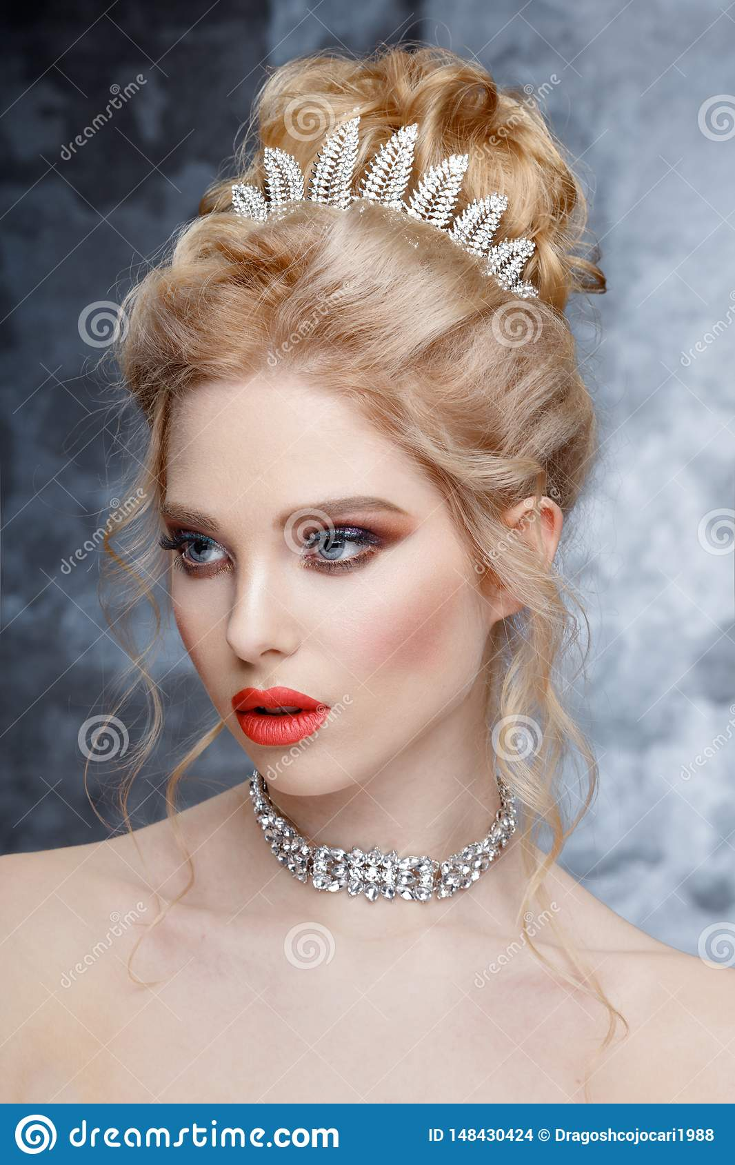 Fashion Portrait of Beautiful Woman with Tiara on head. Elegant Hairstyle. Perfect Make-Up and Jewelry. Coral Lips