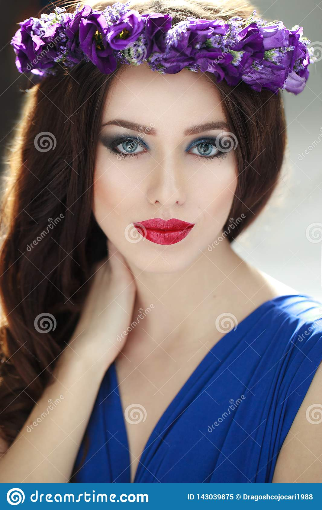 Fashion portrait of a beauty brunette young woman with purpple flower crown. Hairstyle and Perfect Make Up.