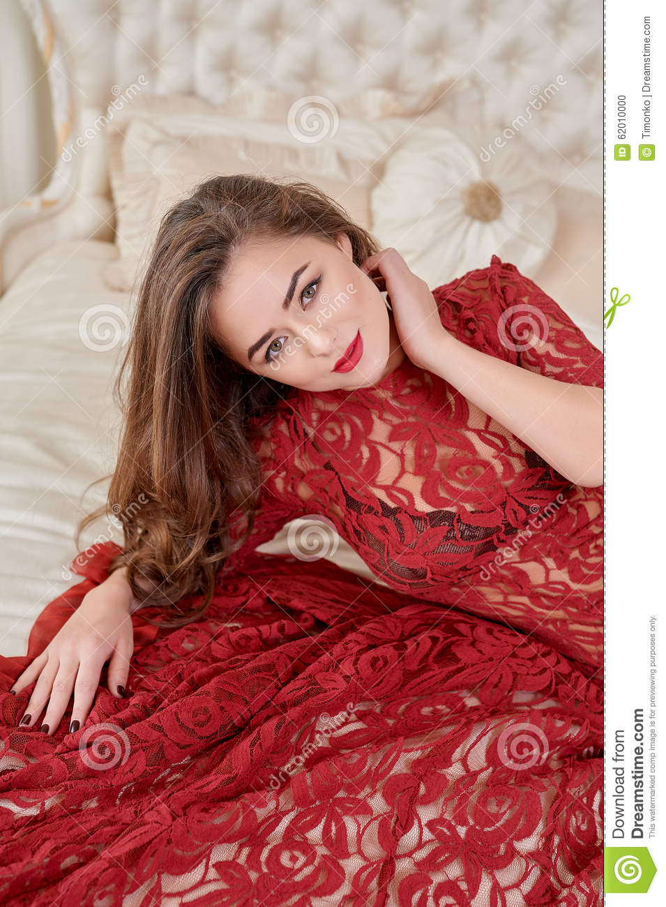 Fashion portrait of elegant young woman in red dress on bed in a luxurious interior