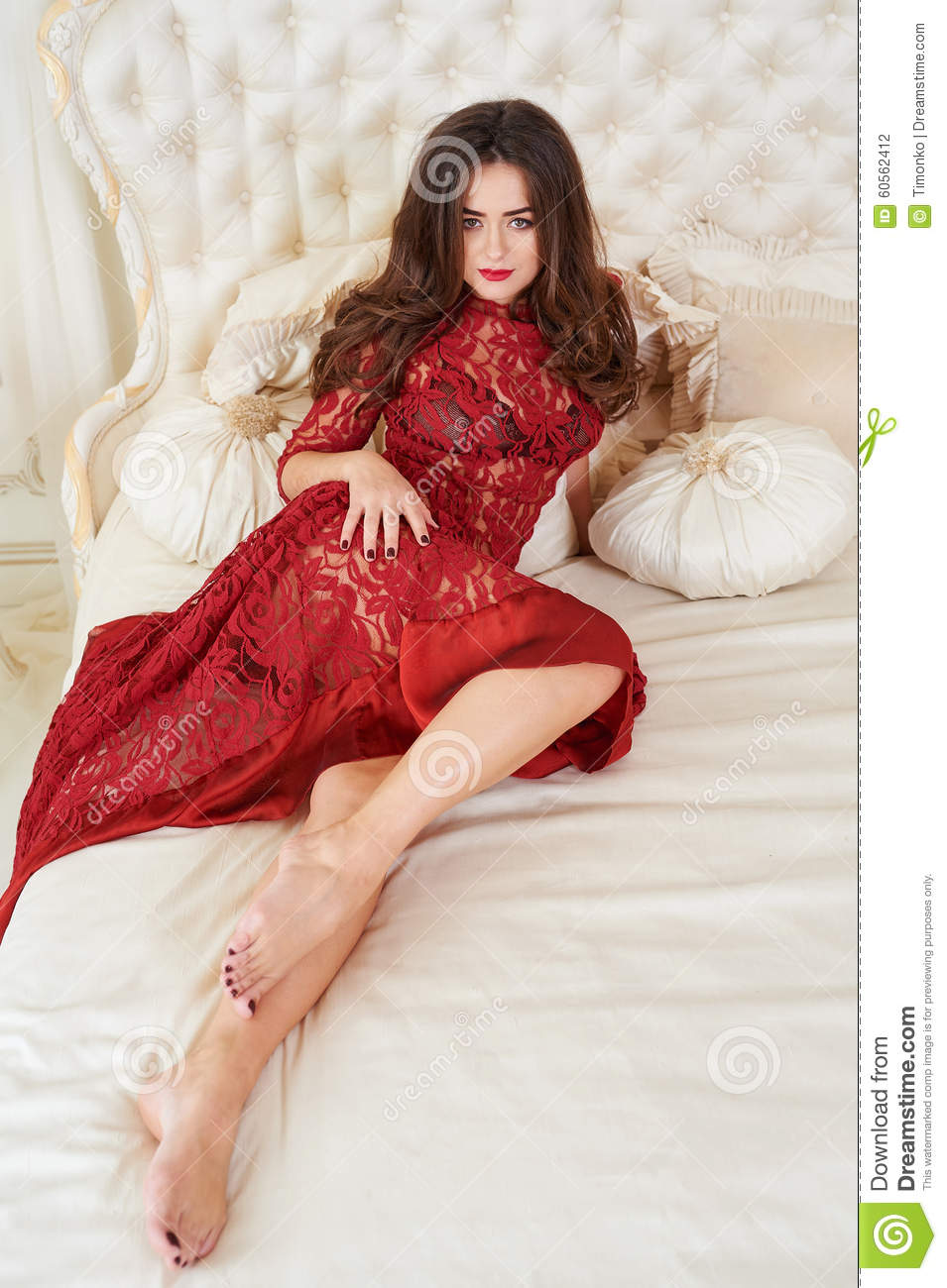 Fashion portrait of elegant young woman in red dress in luxurious interior