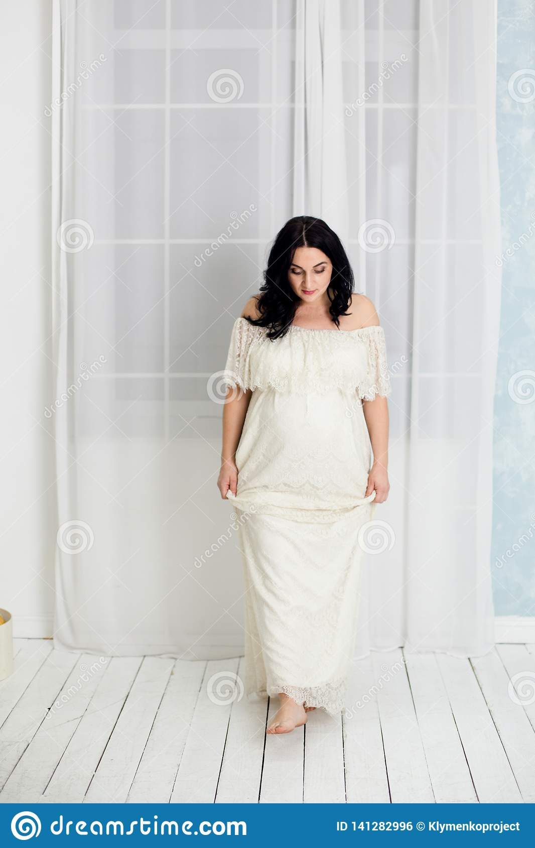 Fashion portrait of happy pregnant woman in white dress