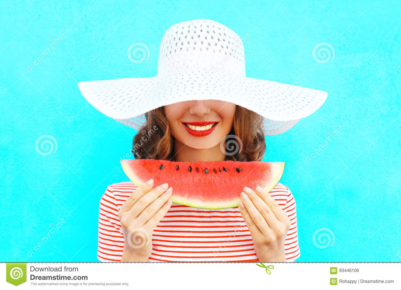 Fashion portrait happy smiling young woman is holding a slice of watermelon in a straw hat