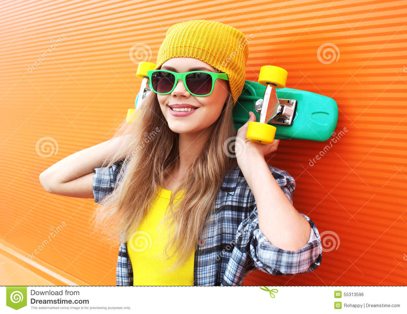 65715d4fd4e6c Fashion portrait of hipster cool girl in sunglasses with skateboard having  fun outdoors against the colorful orange wall