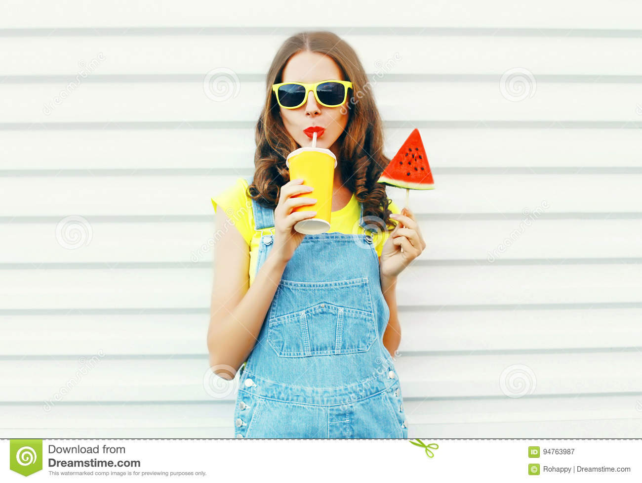 Fashion portrait pretty cool girl drinks a juice from cup holds slice watermelon ice cream