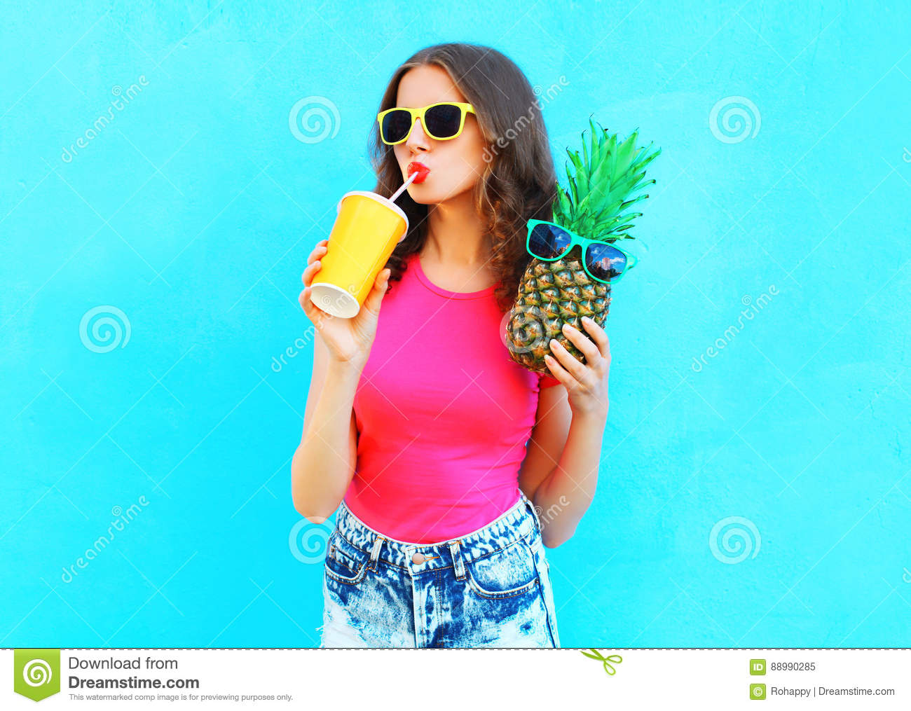 Fashion portrait pretty cool girl with pineapple drinking juice from cup over colorful