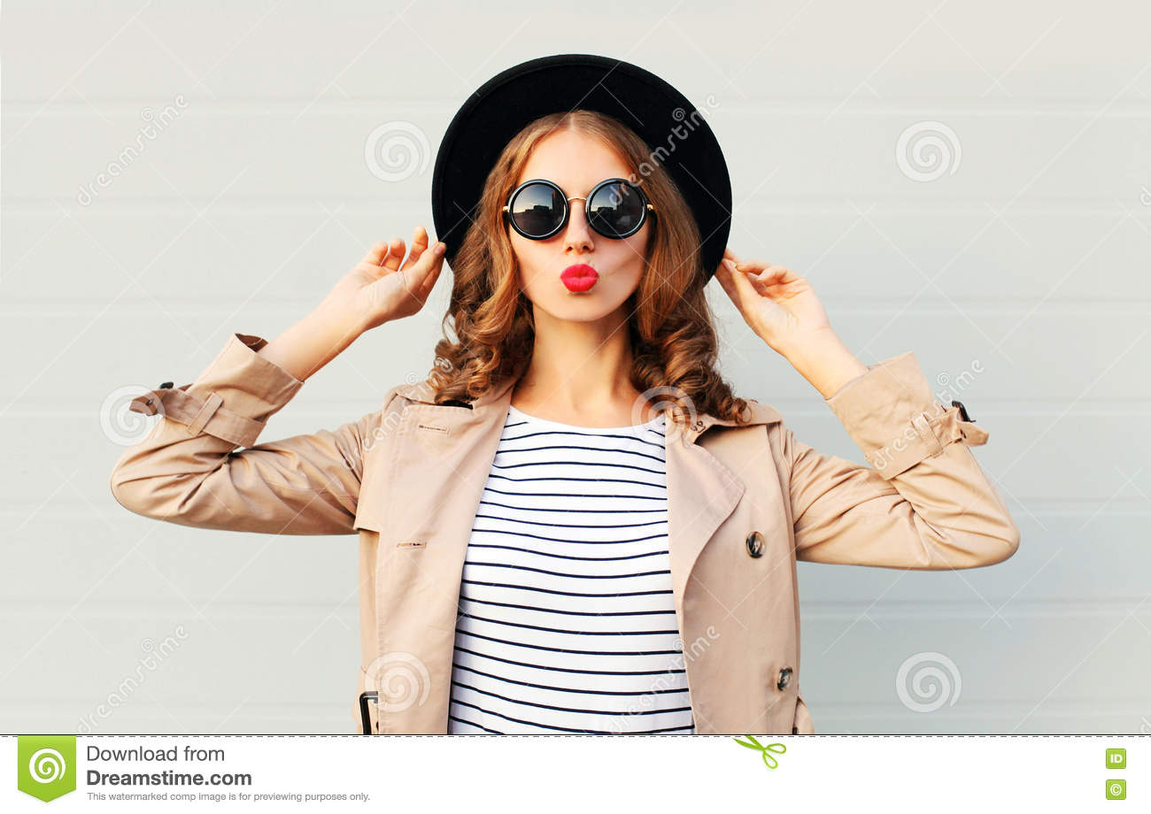 Fashion portrait pretty sweet young woman blowing red lips wearing a black hat sunglasses coat over grey