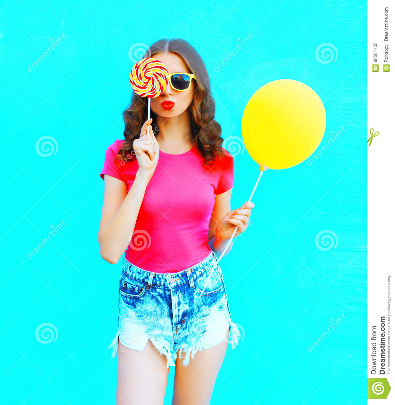 Fashion portrait pretty young woman wearing pink t-shirt, denim shorts with yellow air balloon, lollipop candy over colorful blue