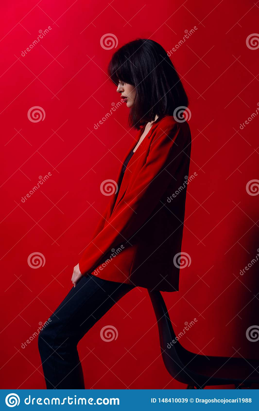 Brunette slim young model posing in fashionable red suit and black pants, near chair, on a red background.