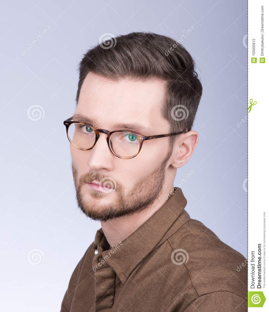 7ea5dc243a5e Fashion portrait of stylish young man in brown shirt. The beard and glasses.  A modern way. Neutral grey background