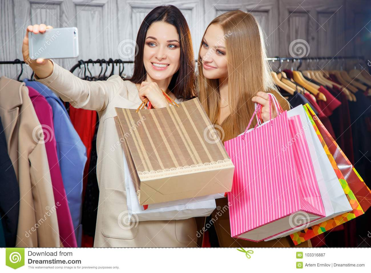 Fashion Portrait Of Two Young Beautiful Women Friends In Shopping Mall With A Lot Bags Making Selfie