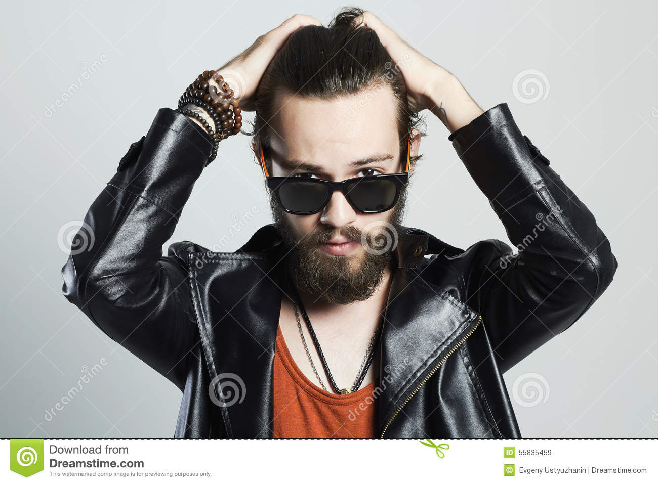 Fashion Portrait of young bearded man in leather jacket. Hipster in sunglasses