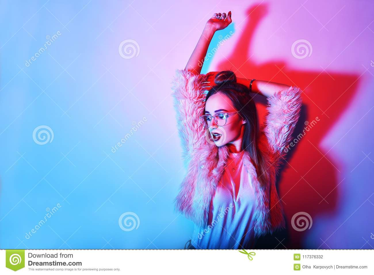 Fashion portrait of young elegant girl in glasses. Colored background, studio shot. Beautiful brunette woman. hipster girl dancing