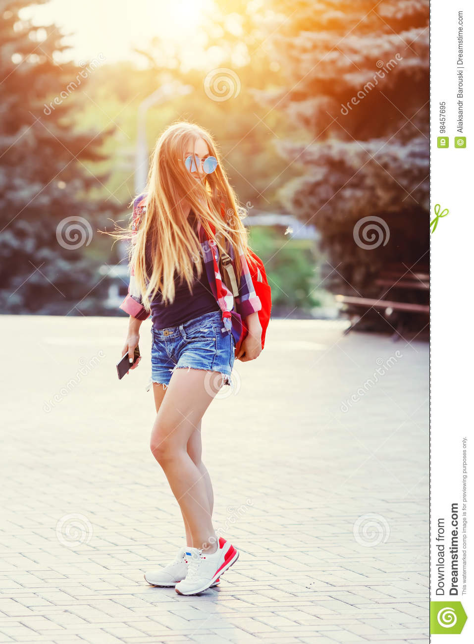 Fashion portrait of young pretty hipster woman outdoor with long hair and red backpack in the sunny summer street. The