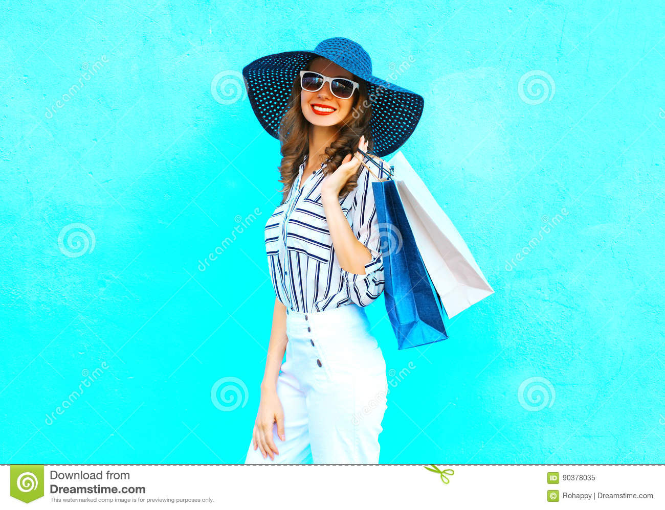 Fashion portrait young smiling woman wearing a shopping bags, straw hat, white pants over colorful blue background posing in city