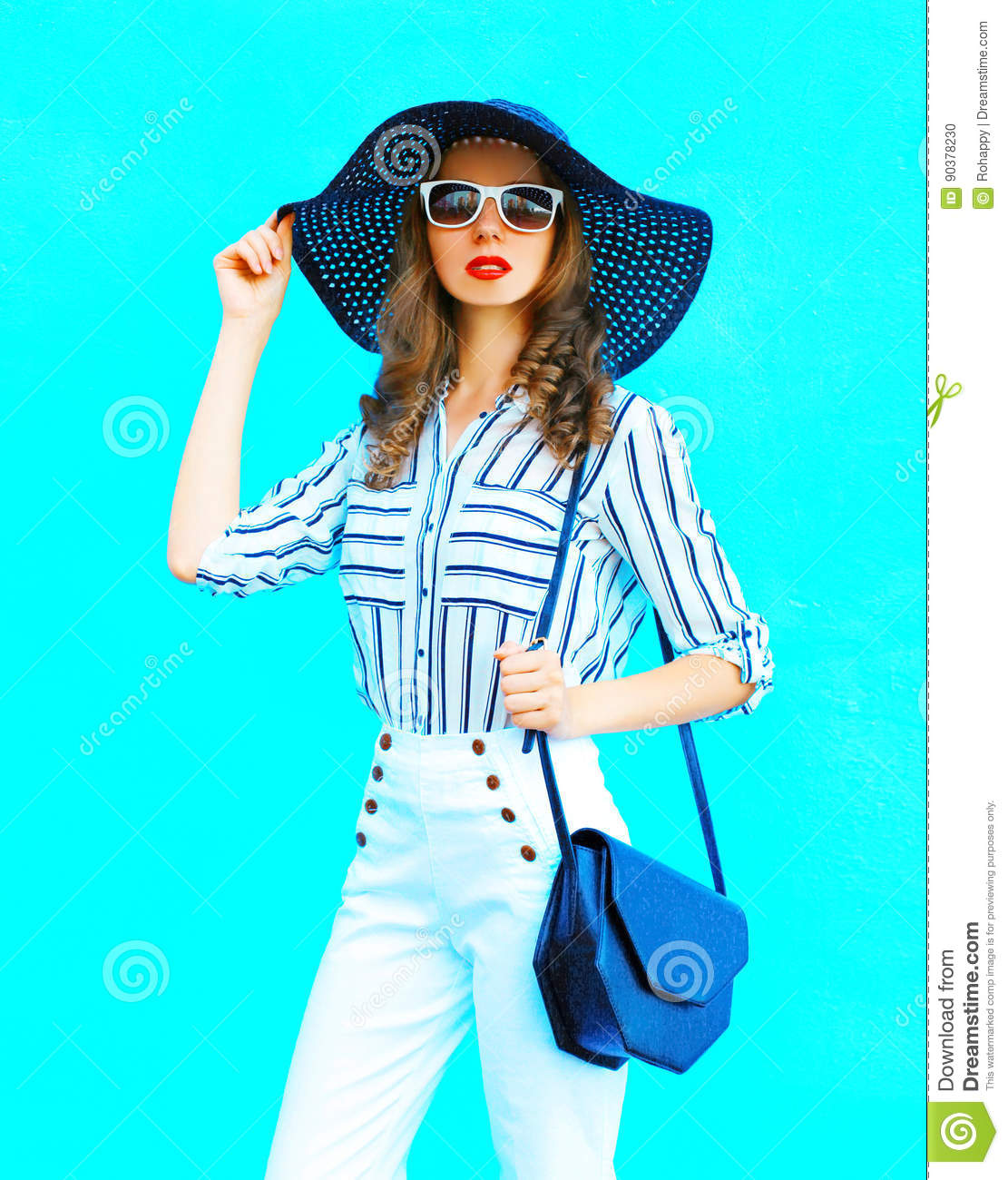 Fashion portrait young woman wearing a straw hat, white pants and handbag clutch over colorful blue background posing in city