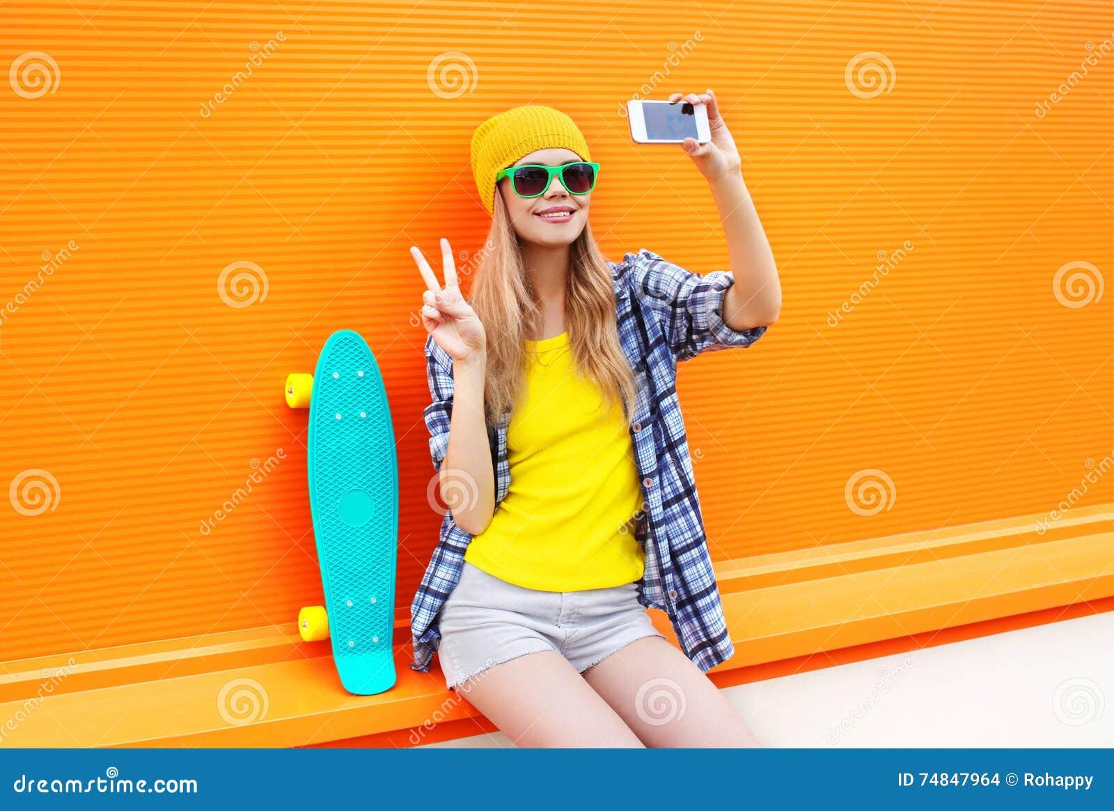 Fashion pretty cool girl makes self portrait on smartphone over colorful orange