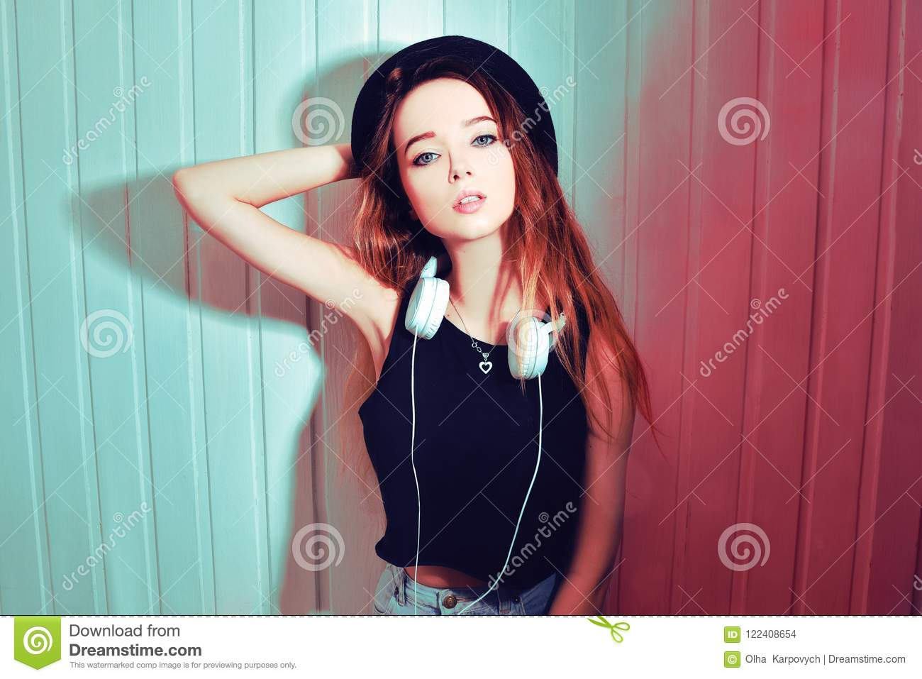 Fashion pretty cool woman in hat and headphones listening to music over pink background. Beautiful young teenage girl in hat