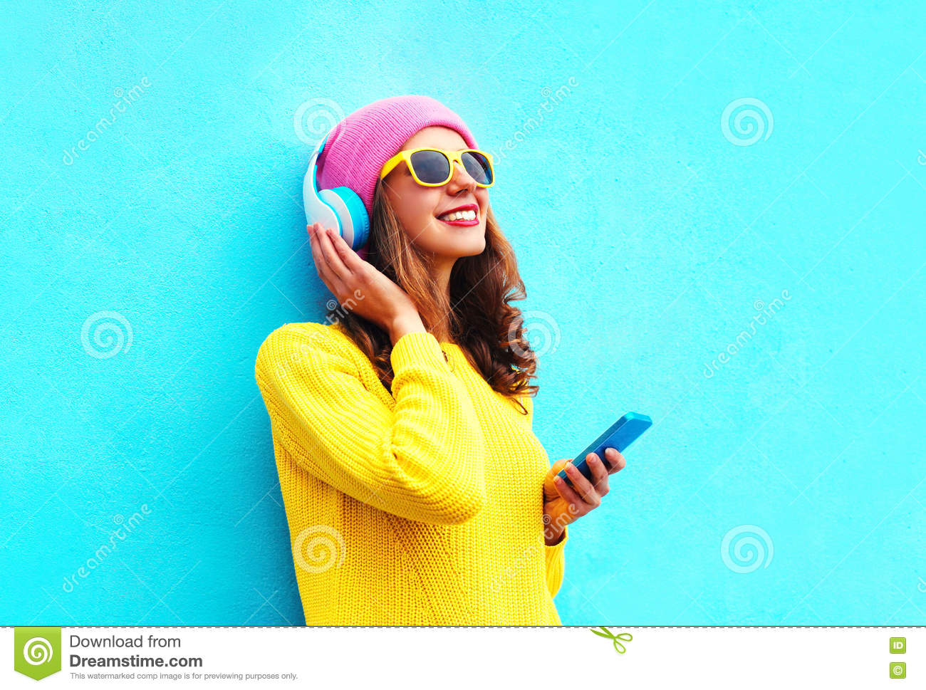 67be285ad3a Fashion pretty sweet carefree girl listening to music in headphones with  smartphone wearing a colorful pink