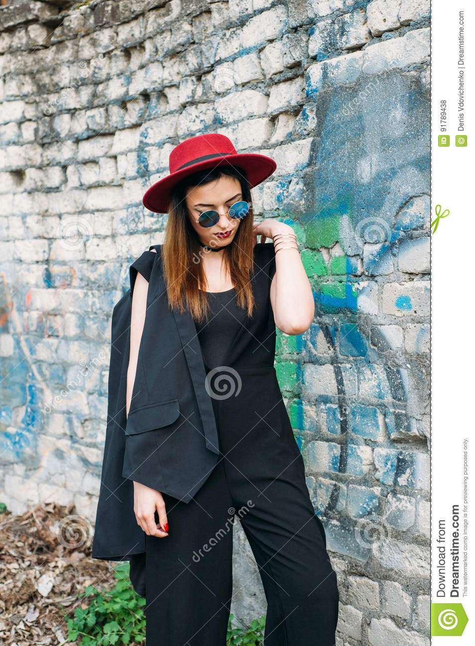 044127e8 Fashion pretty woman model wearing a red hat, green round sunglasses, black  jacket. Posing over brick background with graffiti