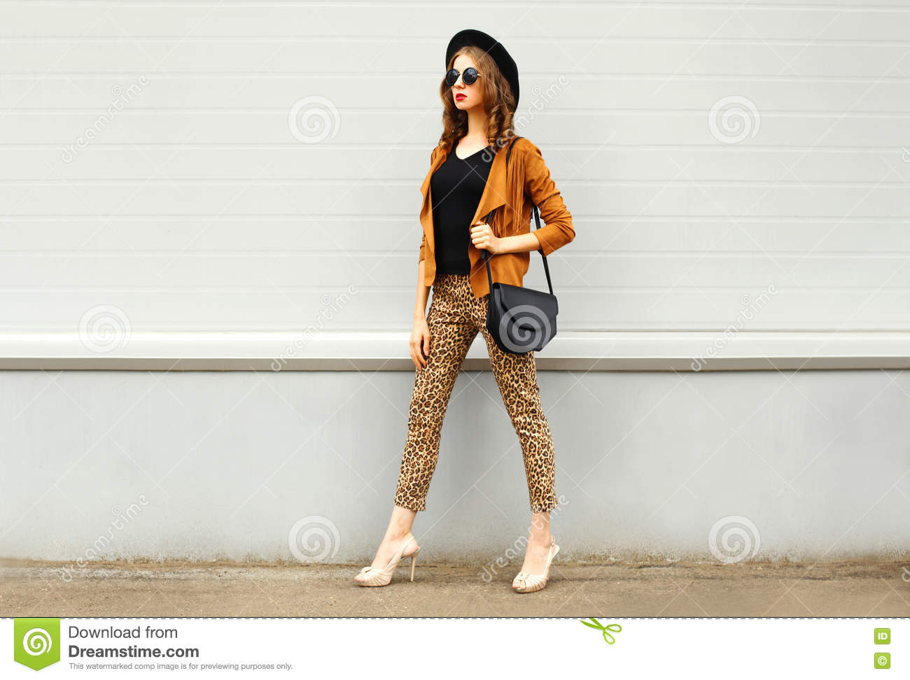 Fashion pretty young woman wearing a retro elegant hat, sunglasses, brown jacket and black handbag walking in city over backg