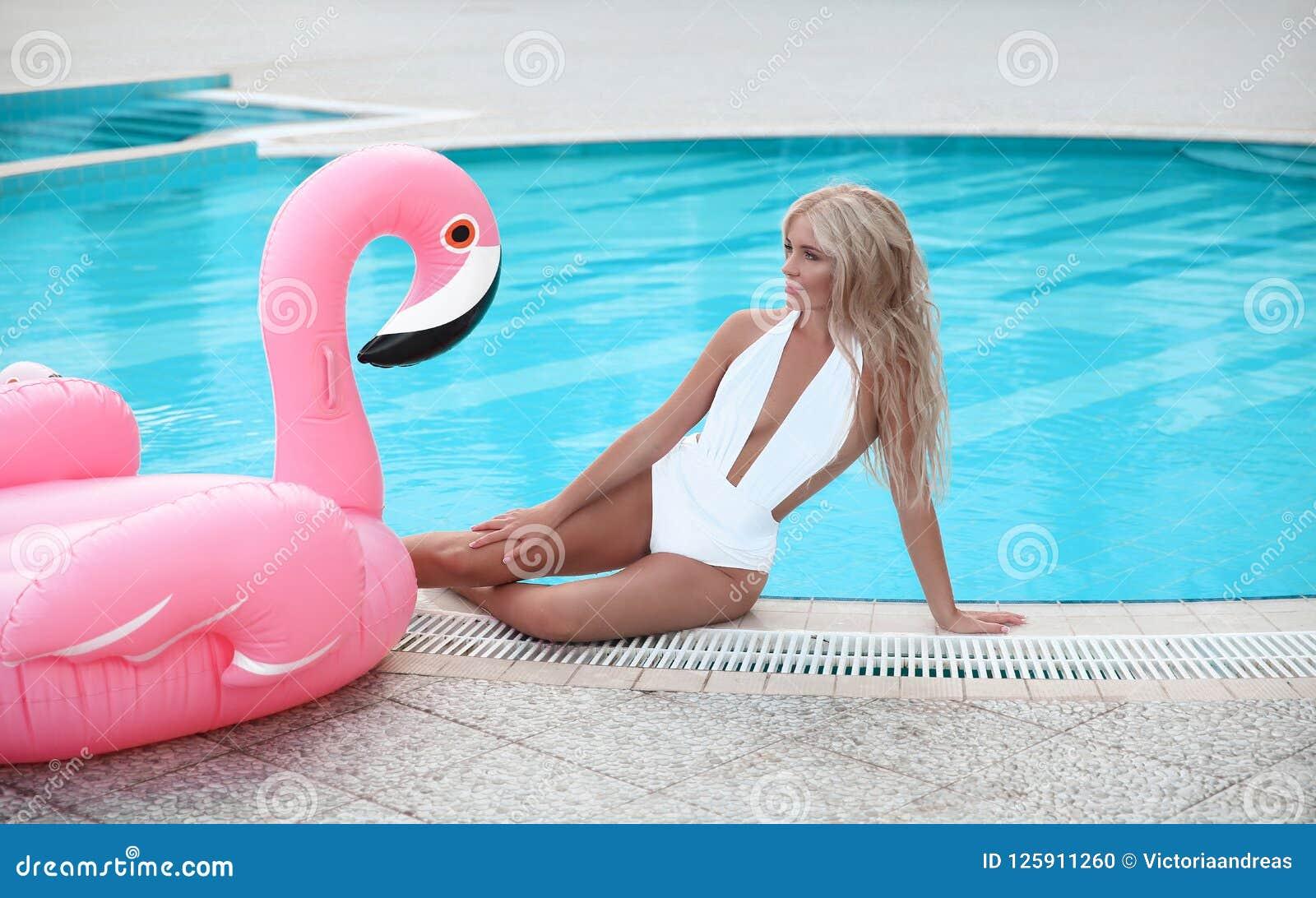 Fashion blond model woman in white bikini posing on Pink in