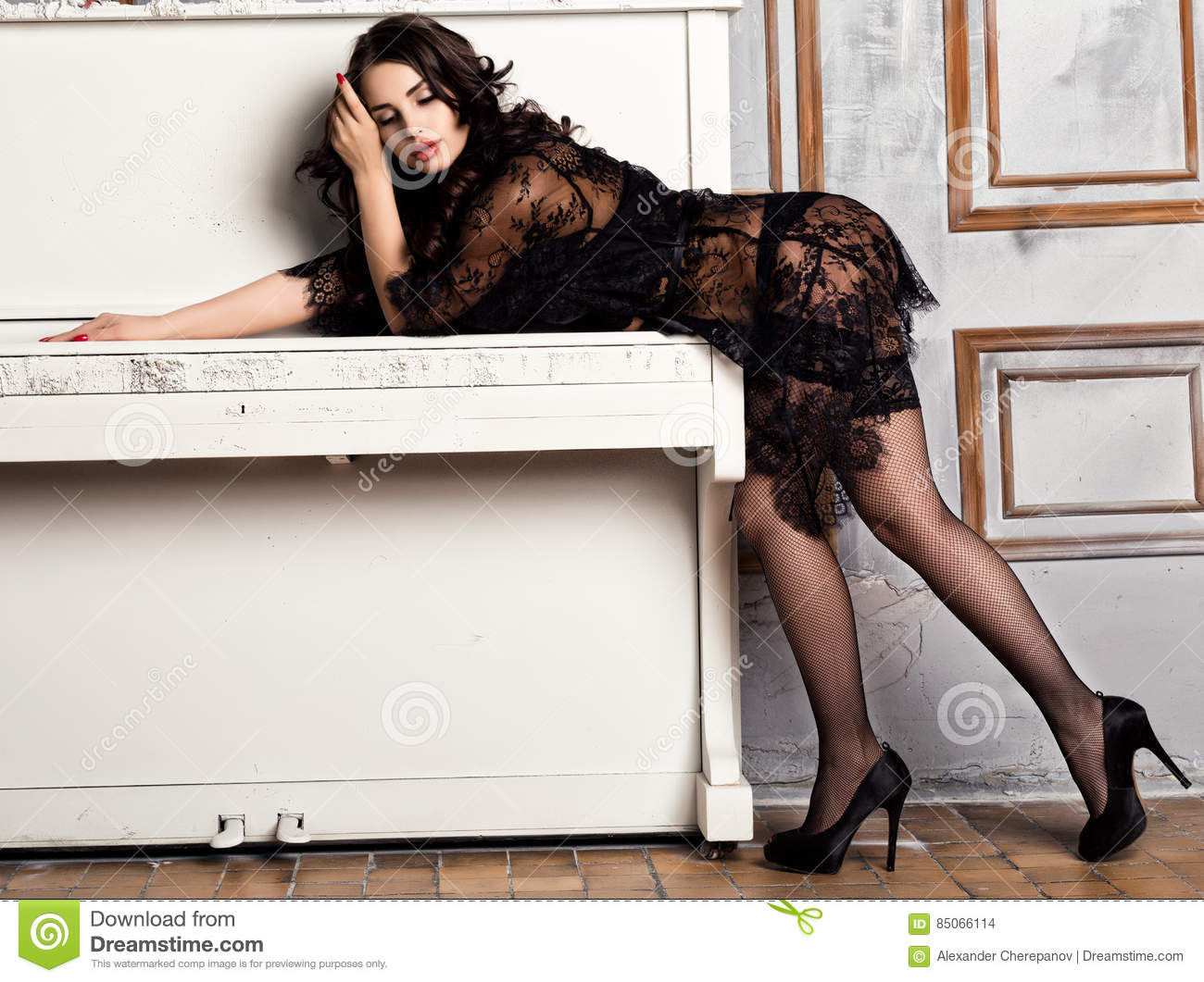 a179bc3764e Fashion young woman in black lacy lingerie and stockings posing on piano.