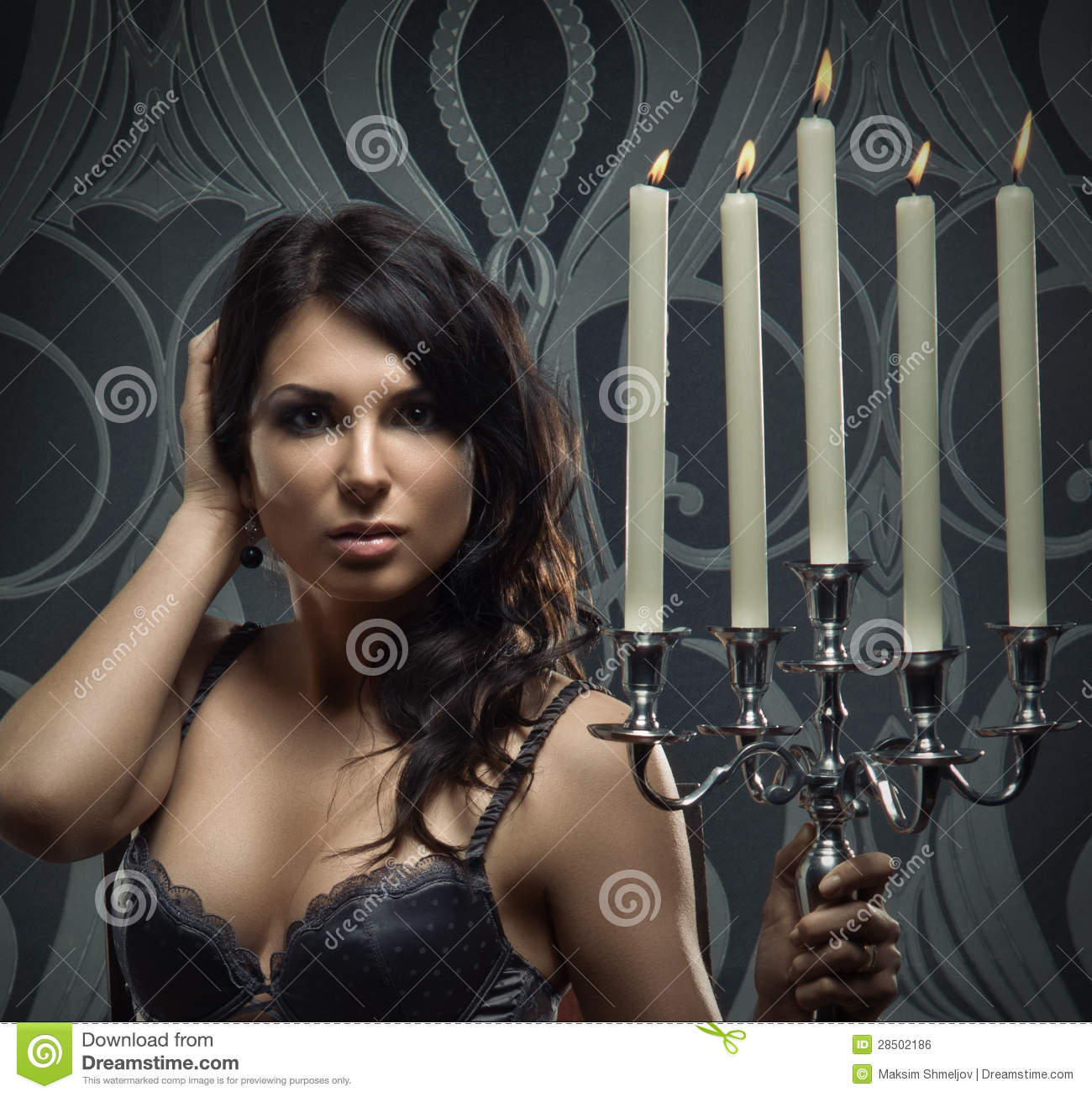 1d90a251f Fashion shoot of a young and attractive brunette Caucasian woman posing in  dark erotic lingerie. The girl is holding candles.