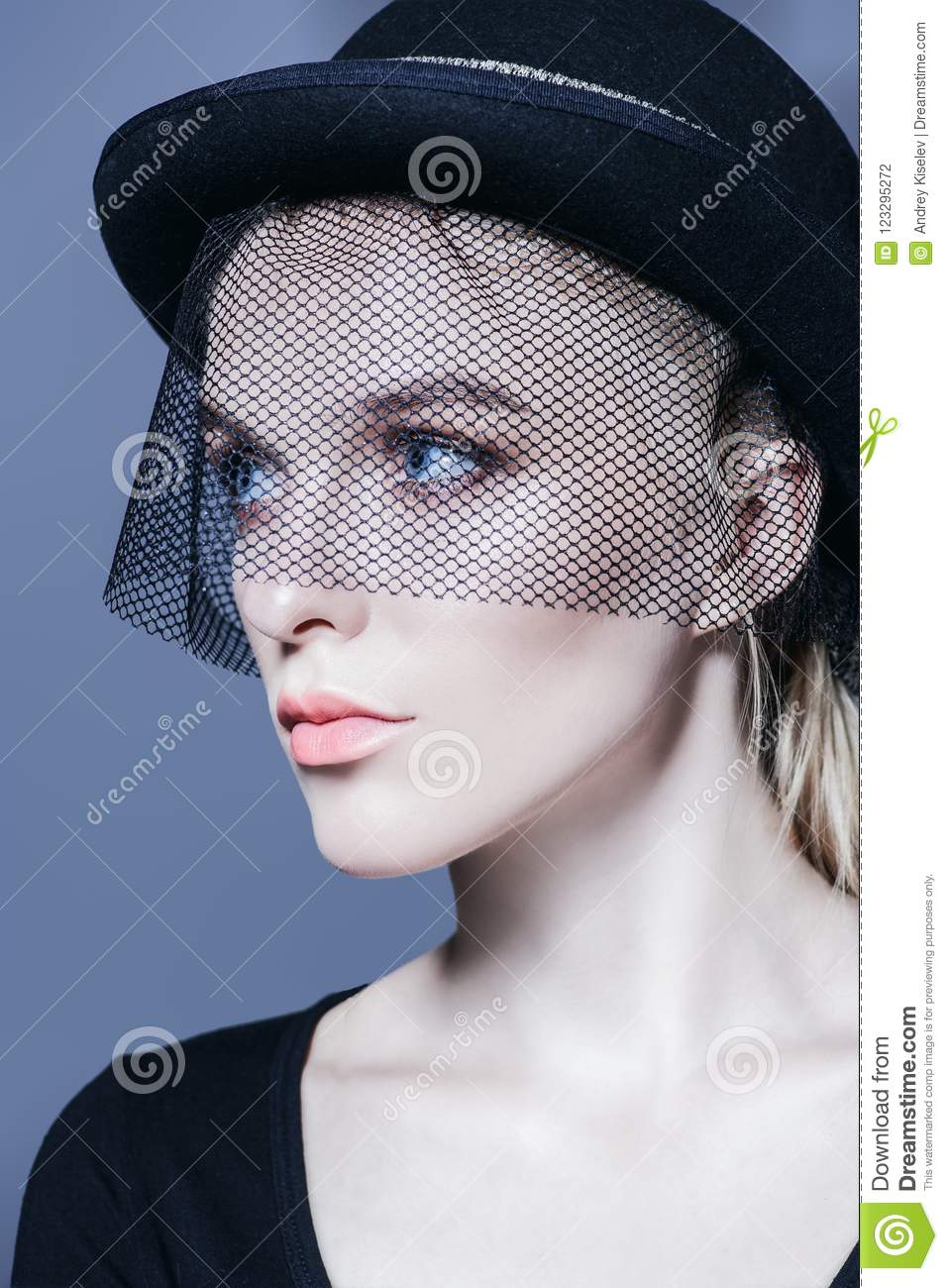 Fashion shot of a stunning young woman in hat with a veil. Headwear style. e05cd611cd0