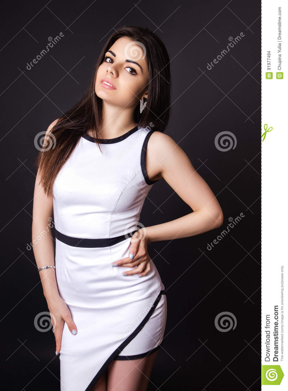 2ae68d9b0f5 Fashion photo of young magnificent woman dressed in a white dress on black  background. Girl posing. Studio photo