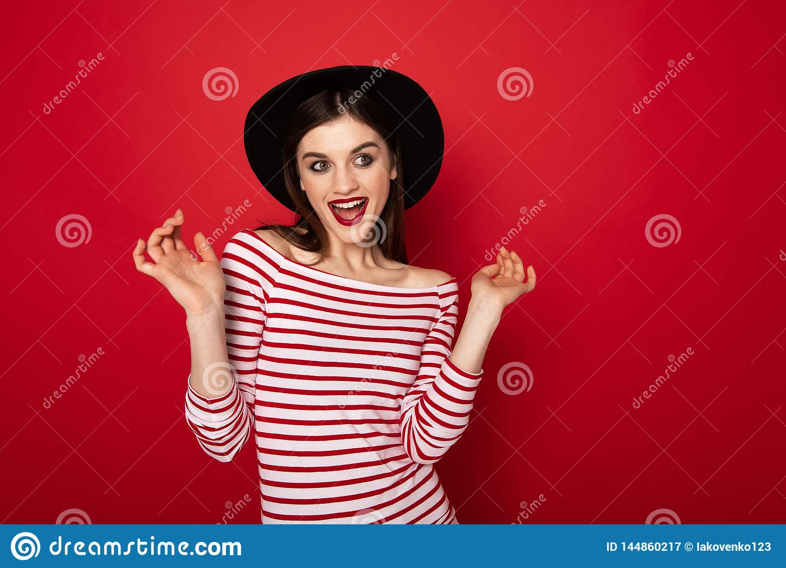 Coquettish girl in striped blouse and black hat