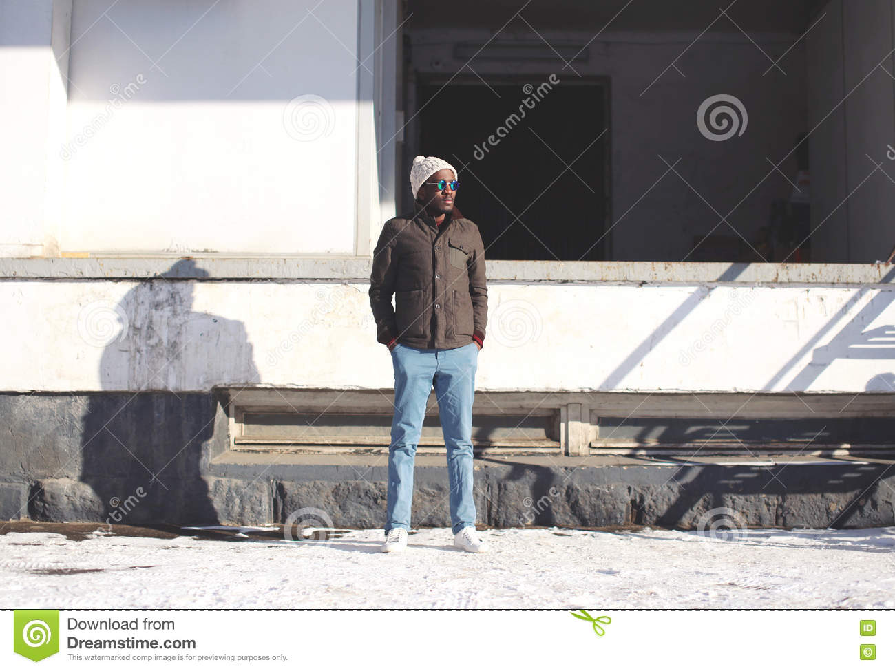 Fashion stylish young african man standing wearing a jacket with knitted hat, winter street style