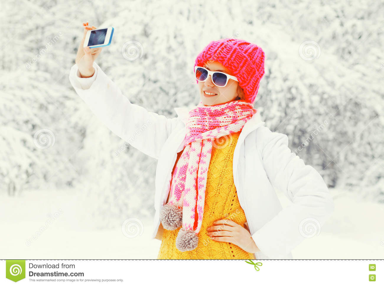 Fashion winter woman taking picture self portrait on smartphone over snowy trees wearing a colorful knitted hat scarf