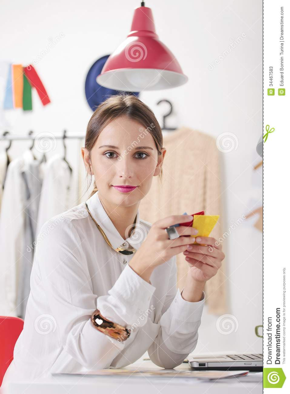 Fashion woman blogger in a creative workspace choosing colors.