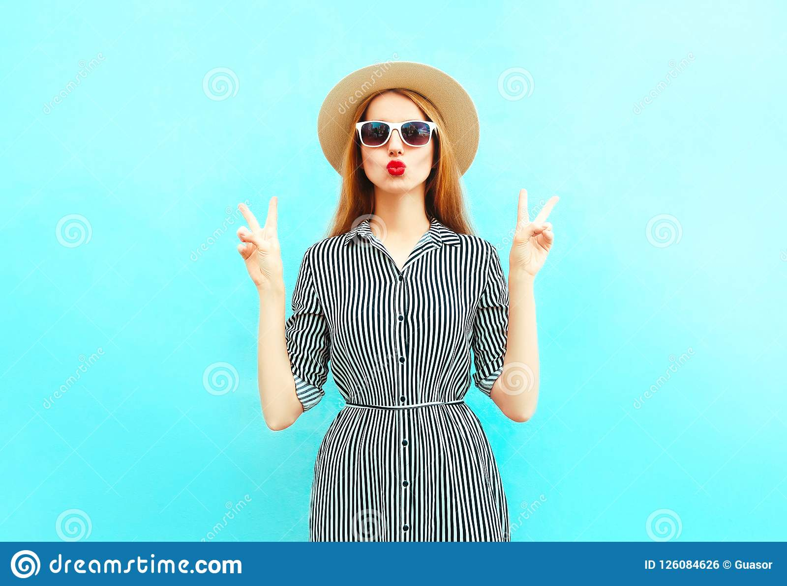 ca6ae82e Fashion woman with red lips sends an air kiss in summer round straw hat on  blue background