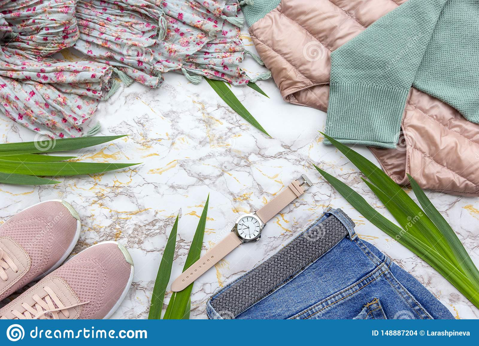 Fashion women's clothes, tropical leaves trendy accessories set on beige white marble background. Stylish casual outfit.