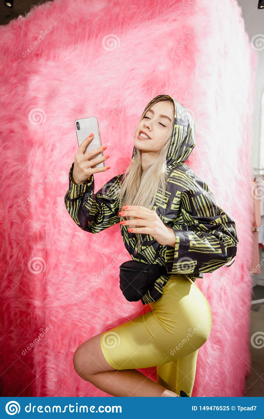 Fashion young girl blogger dressed in a stylish black and yellow jacket and yellow shorts takes a selfie on the
