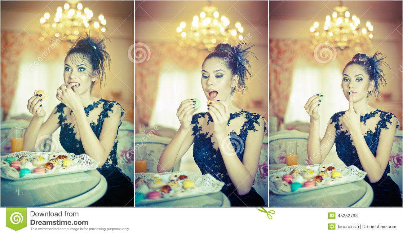 Fashionable attractive young woman in black dress eating macaroons in restaurant. Beautiful brunette holding cookies