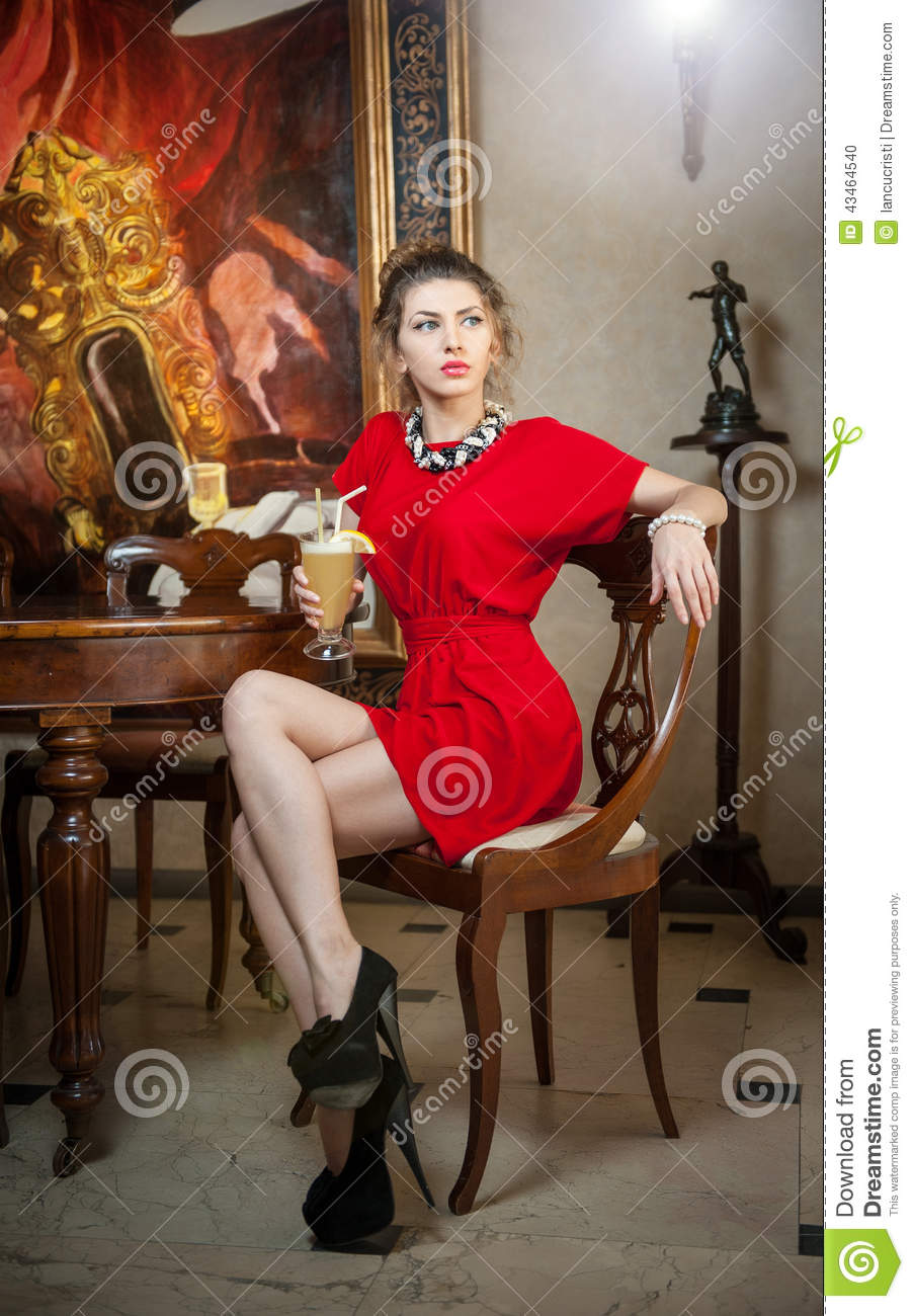 Fashionable attractive young woman in red dress sitting in restaurant. Beautiful lady posing in elegant vintage scenery