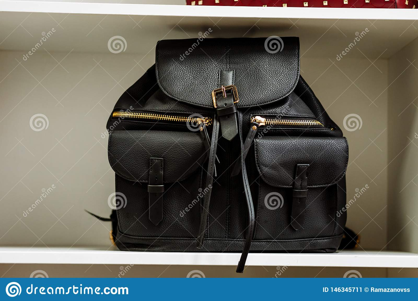 Black leather backpack with golden zipper pockets on a white shelf in the store
