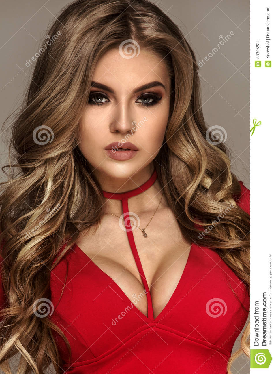 Fashion photo of beautiful blonde caucasian woman with wavy long hair and glamour makeup,girl wearing red dress.