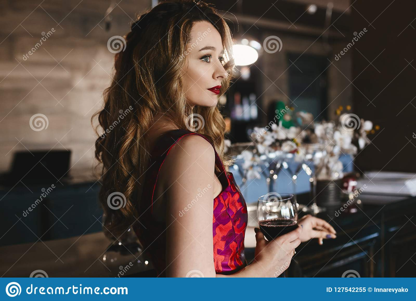 Fashionable blonde model girl with red lips and with curly hairstyle, in the red-pink dress stands at the bar with