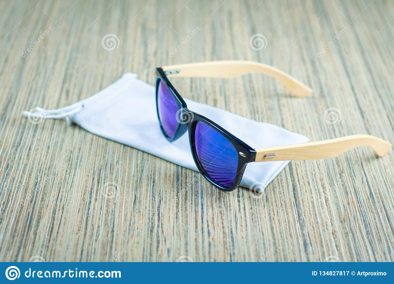 Fashionable blue sunglasses in a rag cover are wooden on the table