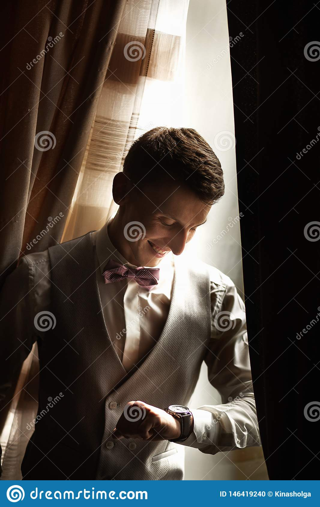 The fashionable bridegroom expects the bride near the window. Portrait of the groom in a grey vest