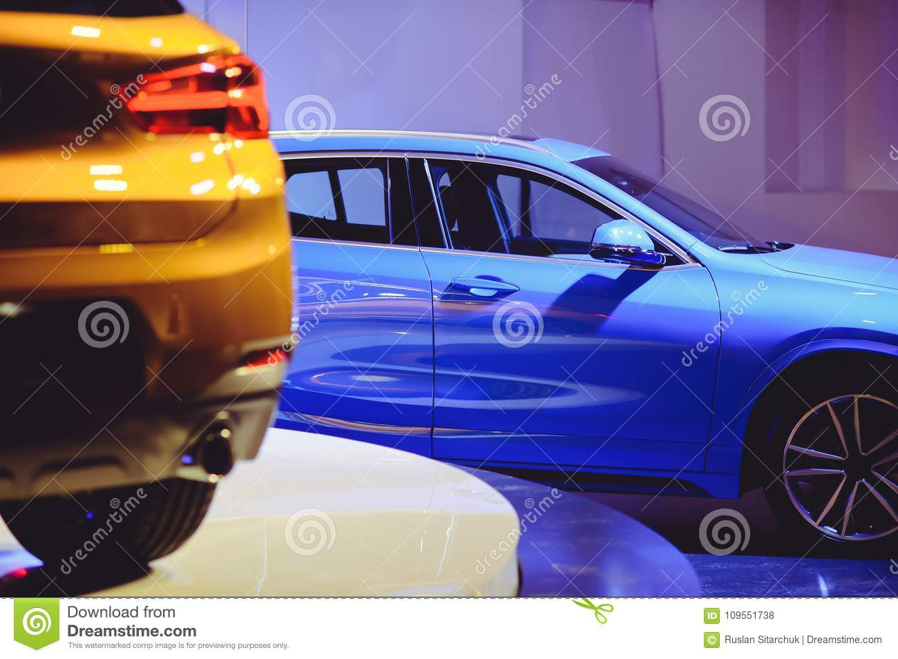 Fashionable bright auto show A number of new cars parked in the car dealers` warehouse, modern design of the premises
