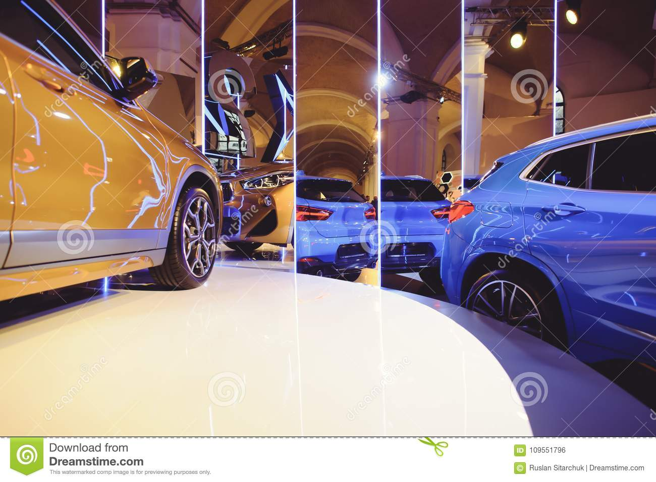 Fashionable bright auto show A number of new cars parked in the car dealers` warehouse, modern design of the room with mirrors