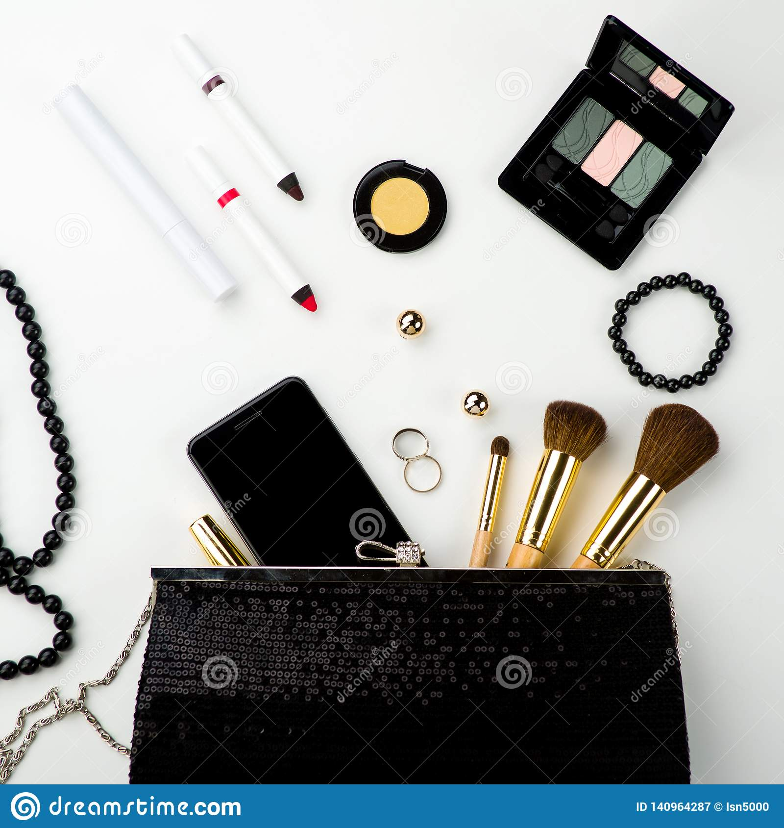 Fashionable female accessories brushes smartphone lipstick eyeshadow and black bag