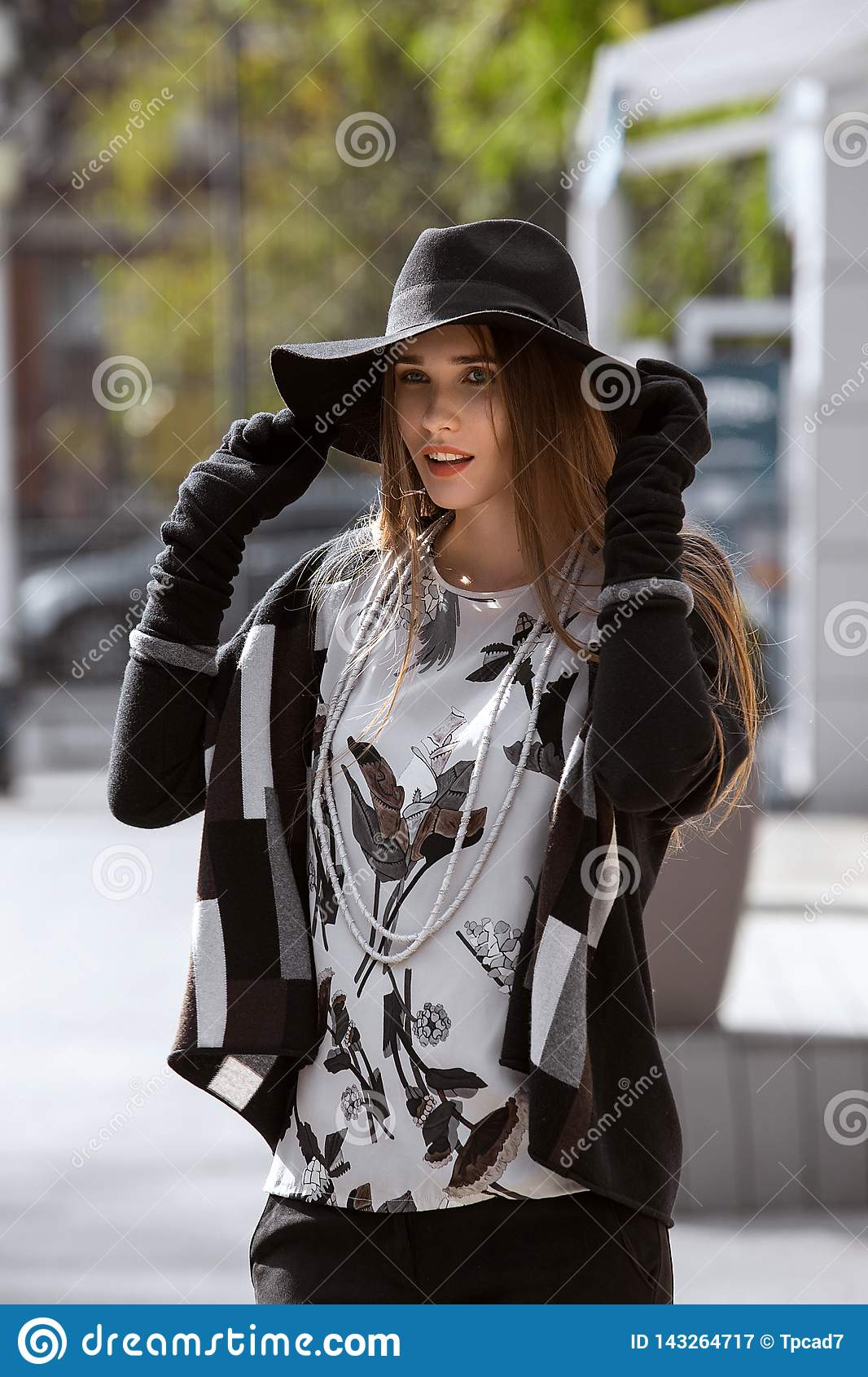 Fashionable girl dressed in black trousers, a stylish gray shirt and sweater and in a black hat with wide brim walks in