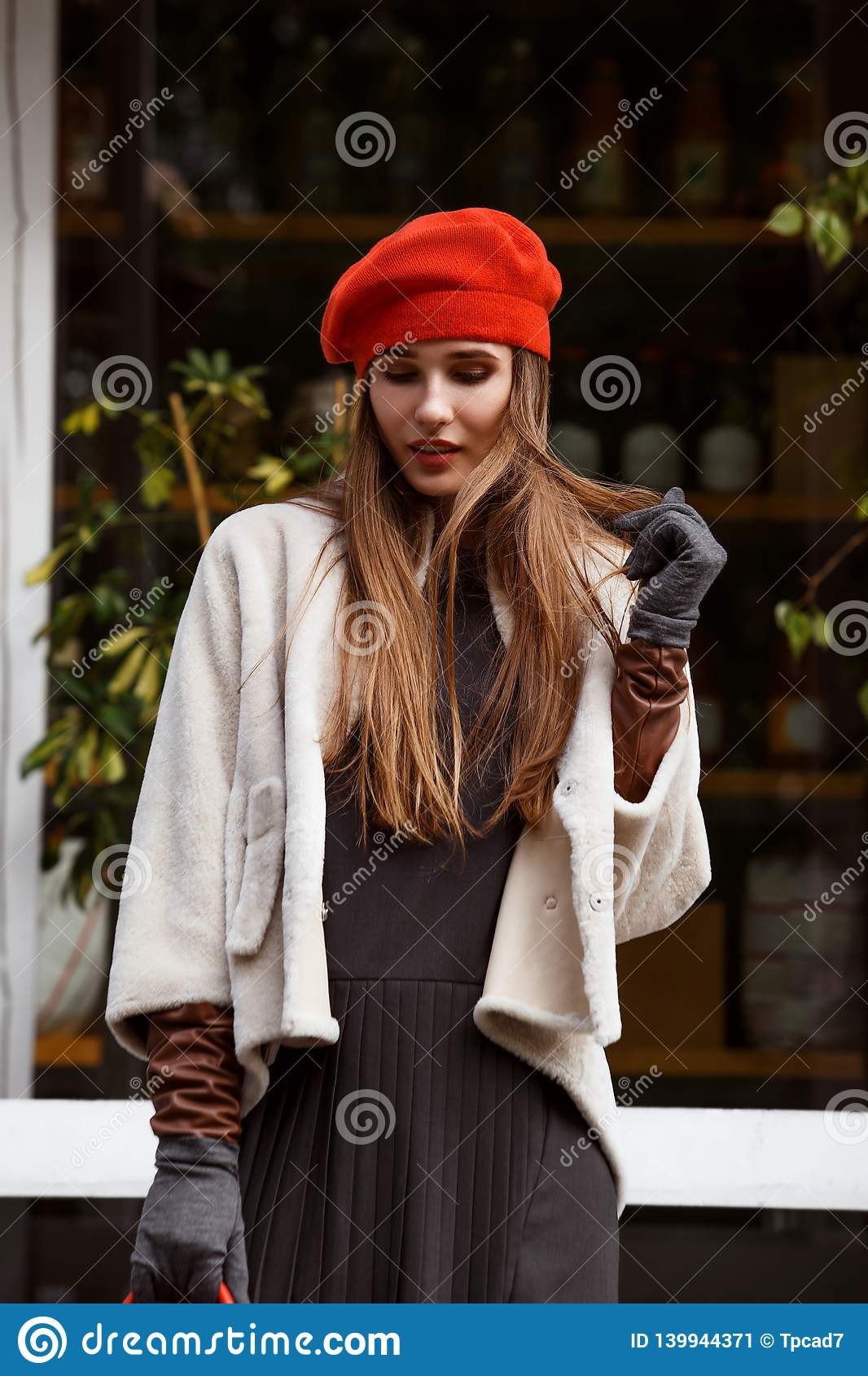 Fashionable girl dressed in stylish gray dress, short sheepskin coat, gloves and red beret walks in the park on the
