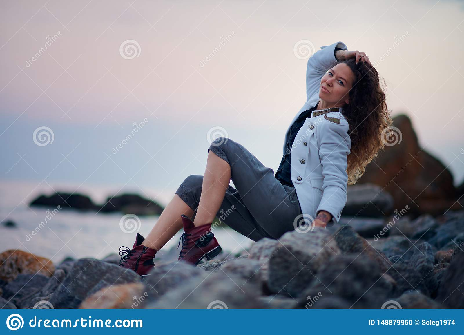 Fashionable girl dressed in white jacket and wide trousers posing near sea in the evening